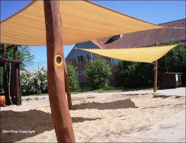 Legepladsens sandkasse har skygge fra et solsejl